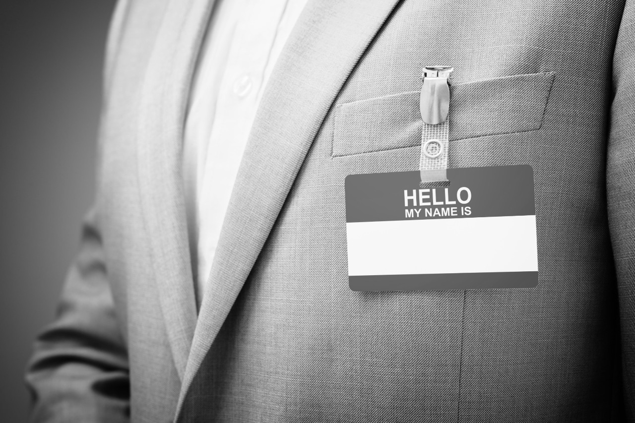 Businessman at an exhibition or conference wearing a Hello my name is security identity name card or tag